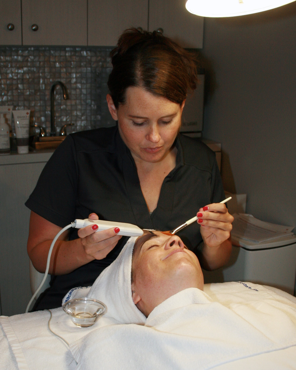 Master Aesthetician Laura using ultrasonic machine on facial client